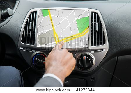 Close-up Of Person's Hand Using GPS Navigation System In Car