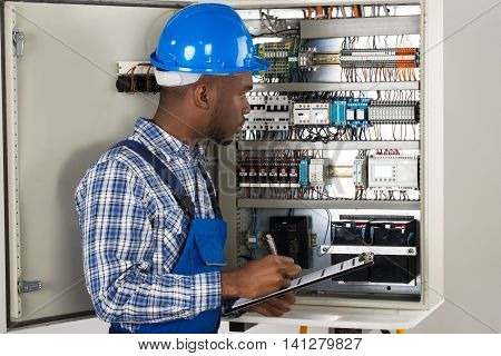 Male Technician Holding Clipboard While Examining Fusebox