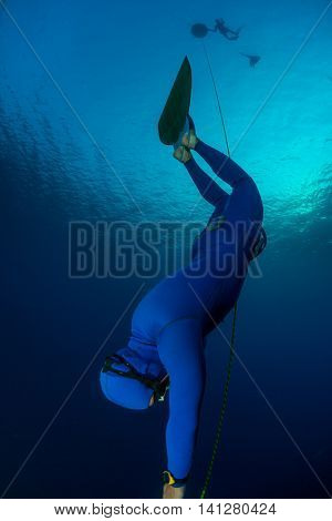 Free diver falling into deep darkness along the rope with monofin