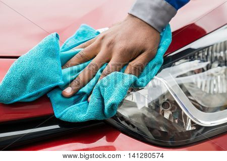Close-up Of Male Worker Cleaning Car Headlight With Cloth