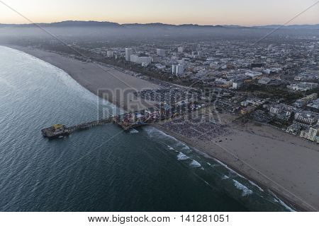 Santa Monica, California, USA - After sunset twilight aerial of large crowd gathered at the Santa Monica pier near Los Angeles.