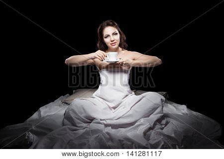 Young Female Sitting In Bed And Drinking Coffee;