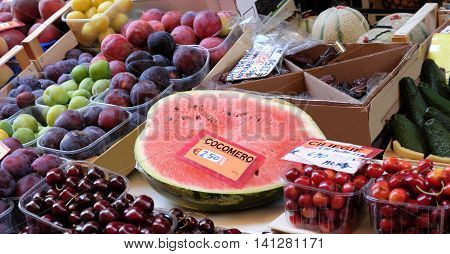 fruit stand in street market with cut watermelon