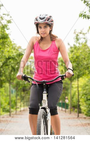 Young Female Cyclist Riding Her Bicycle With Safety Helmet