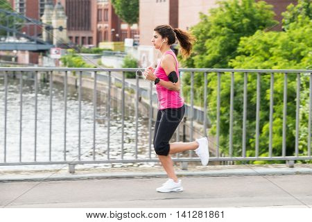 Sporty Young Woman Running On Bridge In Morning