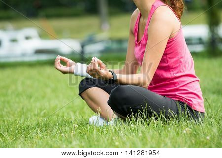 Closeup Of Young Woman Sitting On Grass Meditating In Park