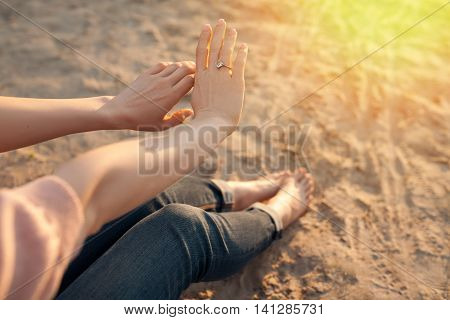 Female Looks At Hand With Golden Engagement Ring;