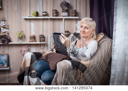 Senior Female Sitting In Cozy Room And Browsing Internet With Tablet;