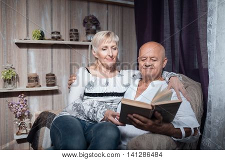 Happy Seniors Couple Sitting In Chair And Read Book;