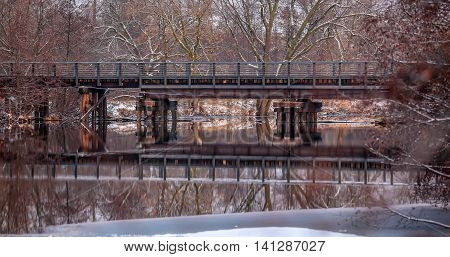 A railroad bridge and its reflection in the Wisconsin river in Wausau, Wi.