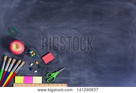 Overhead view of back to school supplies in lower left hand corner of image on erased chalkboard.