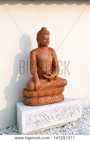 Buddha statue in the setting sun in the garden of stones in the territory of a Buddhist temple. Datsan Rinpoche Bagsha on Bald Mountain in Ulan-Ude, Buryatia, Russia.