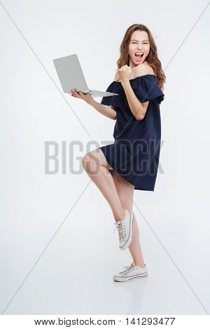 Full length of cheerful excited young woman holding laptop and celebrating success over white background