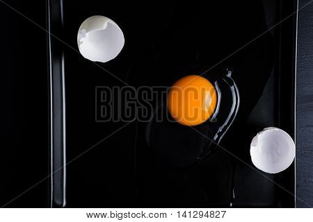 Egg And Shell Cracked On A Black Plate