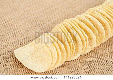 The Potato chips stack on sack background.