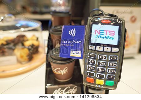 SINGAPORE - CIRCA NOVEMBER, 2015: payment terminal in McCafe at Singapore Changi Airport. A payment terminal is a device which interfaces with payment cards to make electronic funds transfers.