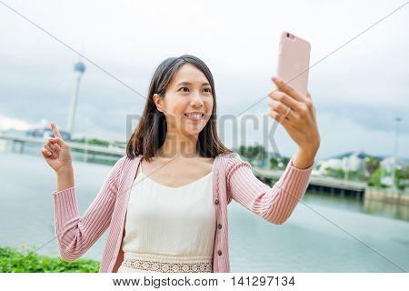 Woman taking selfie by cellphone in Macau city