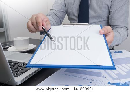 Businessman holding a clipboard with sheet of paper and proposing a pen