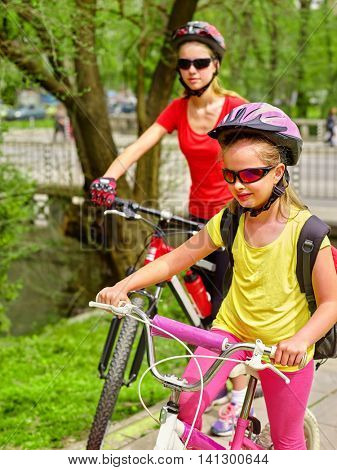 Two girl on bicycle. Girls wearing bicycle helmet and glasses with rucksack ciclyng bicycle. Child in foreground teenager on background.