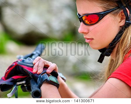 Girl with bicycle. Girl in bicycle glasses watch on watches. Girl in bicycle helmet counts pulse after bicycle training.