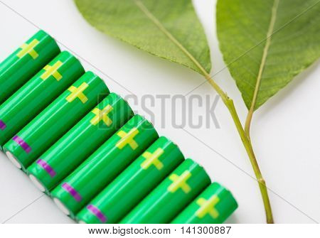 recycling, energy, power, environment and ecology concept - close up of green alkaline batteries and leaf