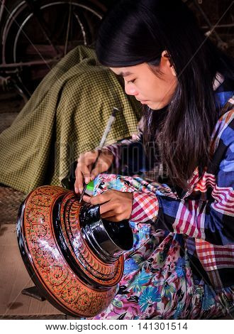 Bagan, Myanmar- December 2015 - A woman demonstrates drawing patterns on a lacquer, Bagan, Mandalay, Myanmar