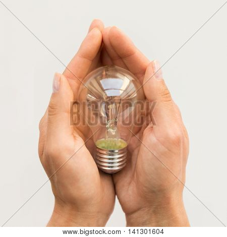 recycling, electricity, environment and ecology concept - close up of hands holding lightbulb or incandescent lamp