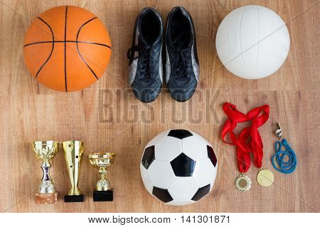 sport, achievement, success and competition concept - different balls, boots with golden cups, whistle and medals over wooden background