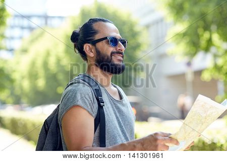 travel, tourism, backpacking and people concept - man traveling with backpack and map in city searching location