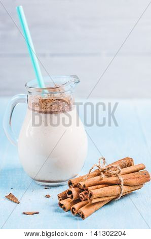 Pitcher glass of milk with cinnamon and cocktail tube on a blue wooden background