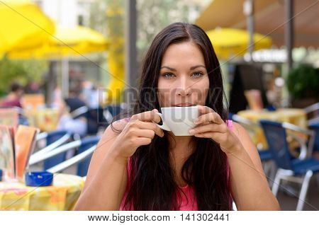Gorgeous woman sipping coffee in cafe with out of focus yellow umbrellas and tables in background with copy space