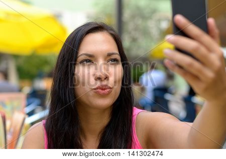 Woman puckering lips while taking picture of herself with cellular telephone with built in camera at outdoor cafe