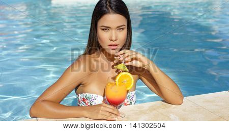 Serious young woman sipping an orange rum cocktail