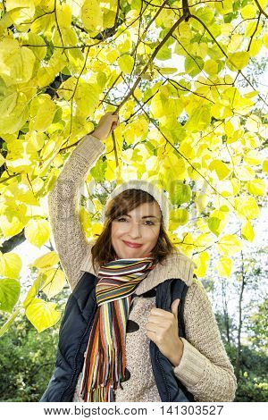 Beautiful young caucasian woman posing under the beech tree in autumn nature. Beauty and fashion. Female portrait. Vertical composition. Vibrant colors.