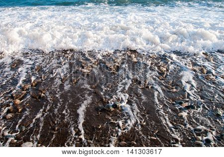 Sea waves flowing to the coast and covering colorful pebbles