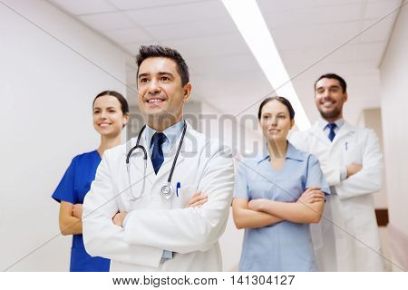 clinic, profession, people, health care and medicine concept - group of happy medics or doctors at hospital corridor