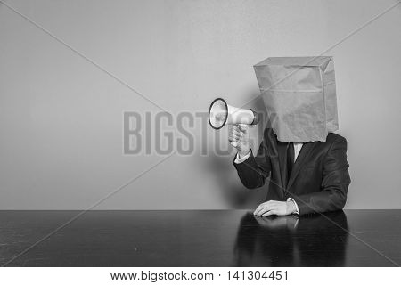 Businessman wearing paper bag in head with megaphone