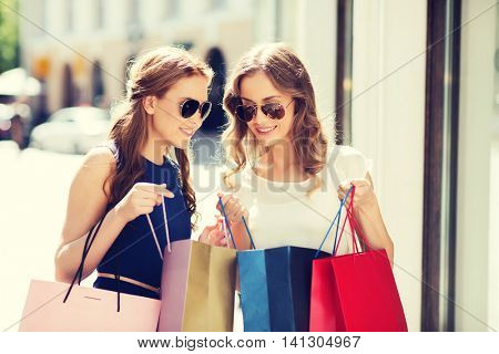 sale, consumerism and people concept - happy young women looking into shopping bags in city