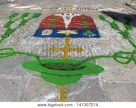 Closeup of organic green candlestick and shield in church square in Baeza Andalusia