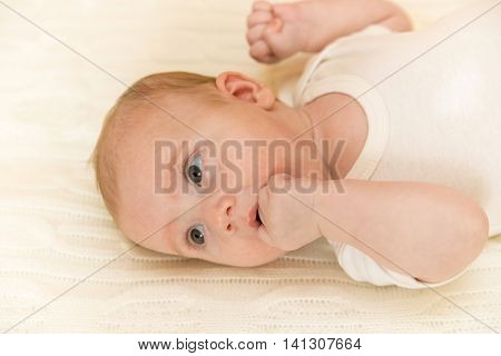 Cute surprised newborn baby 3 months old looks with curiosity