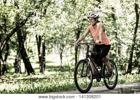 Young woman riding bicycle. High contrast desaturated image