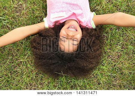 Afro-American little girl lying on green grass