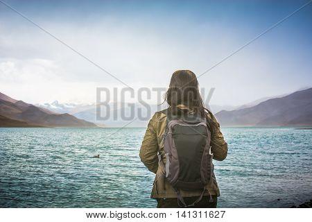 Female tourist looks at Yamdrok lake in Tibet