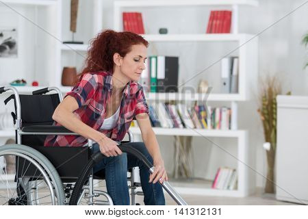woman on wheelchair with vacuum cleaner