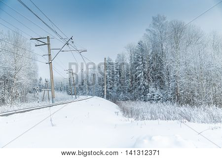 Snow covered railway crossing among the forest