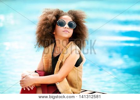 Afro American little girl wearing stylish clothes by the pool. Fashion kid concept