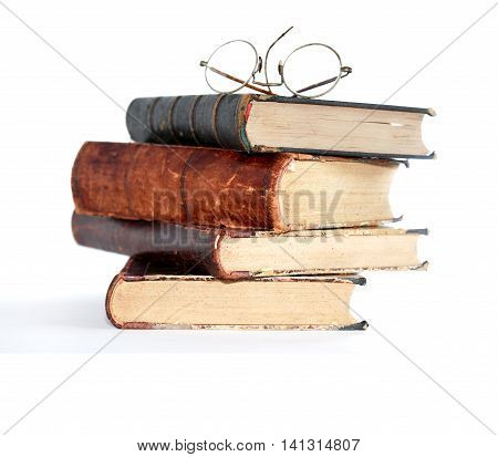 Vintage spectacles above stack of old book on white background
