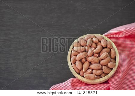Raw peanuts or arachis in wooden bowl on table background