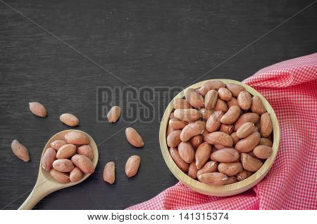 Raw peanuts or arachis in wooden bowl and wooden spoon on table background