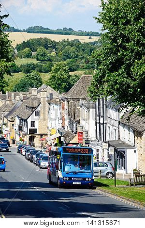 BURFORD, UNITED KINGDOM - JULY 20, 2016 - View along The Hill shopping street with a bus in the foreground Burford Cotswolds Oxfordshire England UK Western Europe, July 20, 2016.